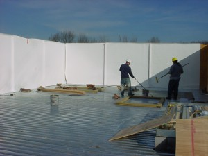 High parapet wall membrane being installed.